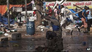 A supporter of Mr Morsi shoots a gun towards police at the Rabaa al-Adawiya mosque area in Cairo's Nasr City, 14 Aug