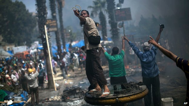 A supporter of ousted Islamist President Mohammed Morsi shoots a slingshot at Egyptian security forces