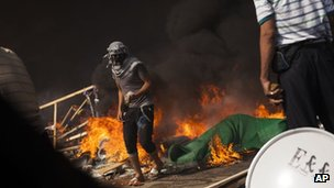 A pro-Morsi supporter holds a gasoline bomb as he passes a fire barricade in Cairo, Egypt on 14 August 2013