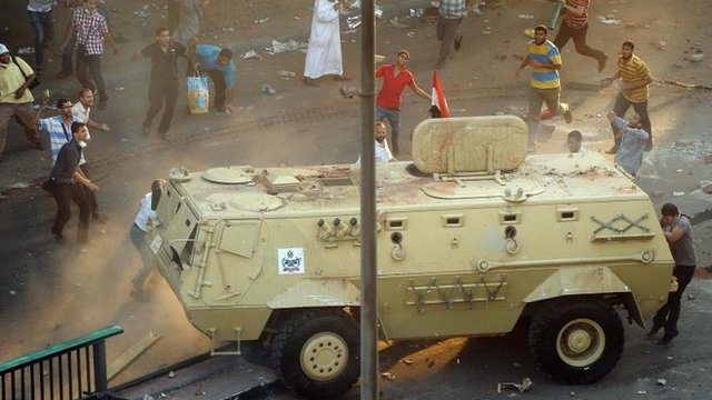 Supporters of ousted Islamist President Mohammed Morsi capture an Egyptian security forces vehicle at the Ministry of Finance in Cairo, Egypt