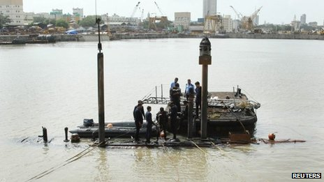 Navy divers standing on the INS Sindhurakshak submarine prepare to dive into the waters of the Arabian Sea, during a rescue operation in Mumbai August 14, 2013.