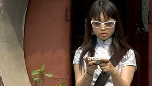 Young Chinese woman using her mobile phone