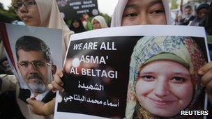 Demonstrators in Kuala Lumpur, Malaysia, hold posters of ousted President Mohammed Morsi and dead protester Asmaa El-Beltagi outside the Egyptian embassy, 15 August