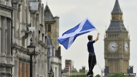 A Scotland soccer fan waves a Scottish saltire flag with Big Ben seen behind in Trafalgar Square in central London,