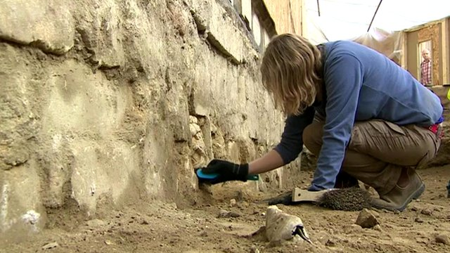 An archaeologist unearths Roman and Norman carved stones underneath Bath Abbey