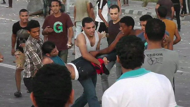 Young men carrying another wounded man in Alexandria