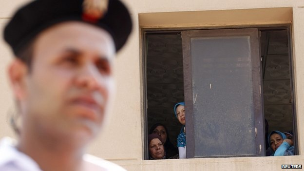 Government employees look out of a window during a funeral for policemen killed during the clashes in Cairo, August 15, 2013