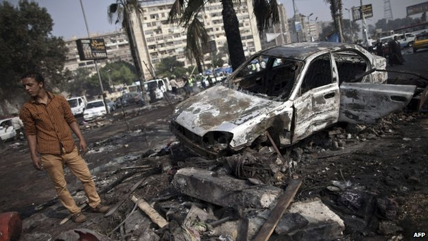 An Egyptian man stands amidst the debris at Rabaa al-Adawiya square in Cairo on August 15, 2013