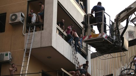 Lebanese citizens flee their house through a balcony at the site of a car bomb