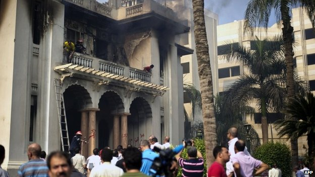 Bystanders, firefighters and workers stand by the Giza Governorate headquarters