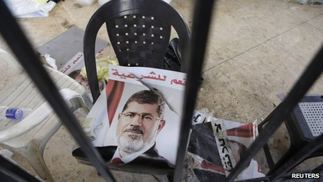 A poster of deposed Egyptian President Mohamed Morse is seen outside a burnt mosque in Cairo 16 August  2013