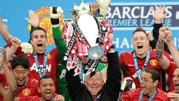 Sir Alex Ferguson holds aloft the Premier League trophy surrounded by his Manchester United squad