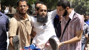 Egyptian Muslim Brotherhood supporters carry an injured comrade who was shot during clashes with security forces in Giza