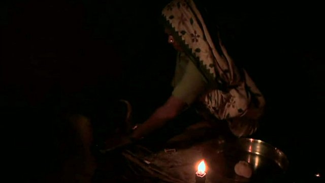 Lady working by candle light