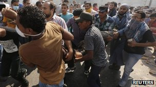 Morsi supporters carry injured man near Ramses Sq