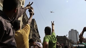 Supporters of deposed Egyptian President Mohammed Morsi gesture at an army helicopter as they shout slogans during a protest outside Al-Fath Mosque in Ramses Square, in Cairo (16 August 2013)