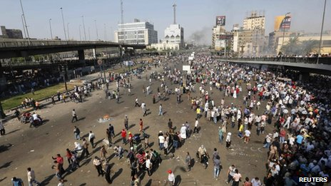 Smoke rises in the distance as supporters of ousted Egyptian President Mohammed Morsi are seen in Cairo 16 August, 2013.