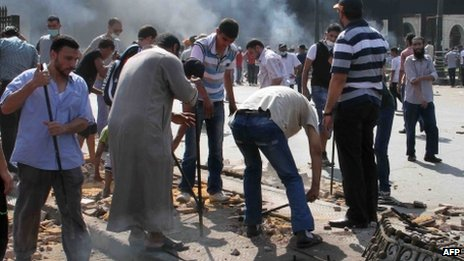 Egyptian Muslim Brotherhood supporters break up the pavement to collect rocks to throw towards police as clashes broke out in Cairo's Ramses square on 16 August, 2013