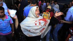 An Egyptian woman with blood on her clothes screams during clashes between security forces and supporters of Egypt's ousted President Mohammed Morsi in Ramses Square, in downtown Cairo, Egypt, (16 August 2013)