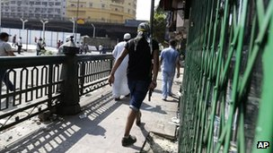 A supporter of Egypt's ousted President Mohammed Morsi walks with a pistol during clashes with Egyptian security forces in Ramses Square, downtown Cairo, Egypt (16 August 2013)