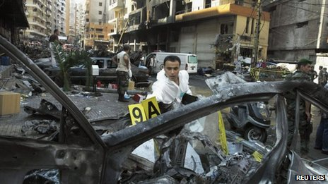 A forensic inspector examines a burnt vehicle at the site of a car bomb that occurred on Thursday in Beirut's southern suburbs, 16 August, 2013.