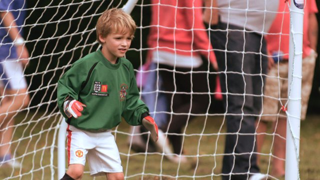 A young boy keeps goal