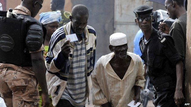Police check the IDs of people arriving at a polling station during the presidential elections in Mali on 11 August 2013 in Bamako