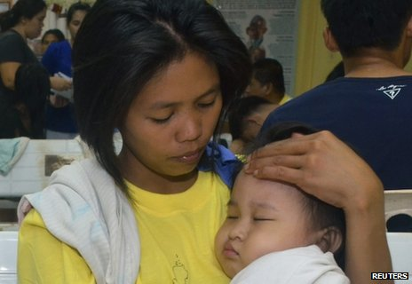 A woman holds her child in a hospital after they were rescued from a passenger vessel MV St Thomas Aquinas before it sank in Talisay, Cebu in central Philippines 17 August, 2013.