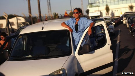 A woman leans out of her car's door in a traffic queue at the Spain-Gibraltar border