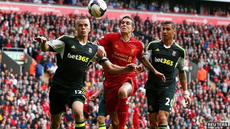 Liverpool's Daniel Agger (C) is challenged by Stoke City's Ryan Shawcross (L) and Geoff Cameron during their English Premier League soccer match at Anfield in Liverpool, on 17 August
