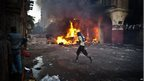 A supporter of Egypt's Muslim Brotherhood runs past a burning vehicle during clashes with security forces close to Cairo's Ramses Square on 16 August, 2013.