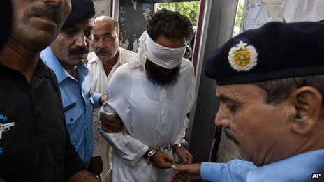 Muslim cleric Khalid Jadoon (blindfolded) is escorted by police in Islamabad (2 Sept 2012)