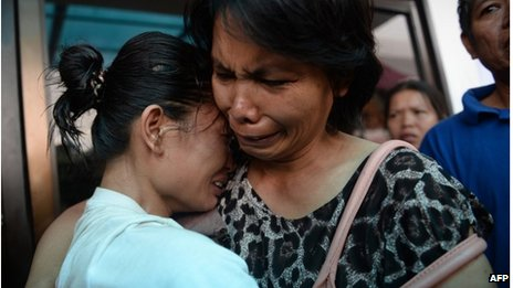 A survivor (L) reacts as she is reunited with a relative outside the ferry company's office in Cebu City