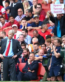 An Arsenal supporter tries to get his message across to Arsene Wenger