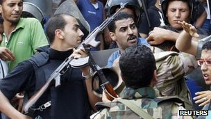 Police and pro-Egyptian government supporters struggle outside al-Fath mosque