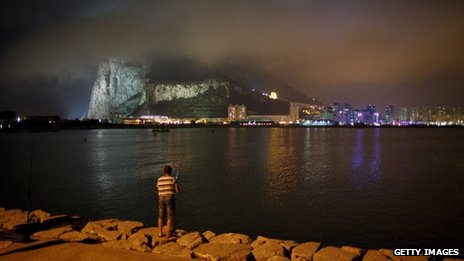 A man fishes near the Gibraltar/Spain border as the Rock of Gibraltar