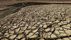 A man fetches water from a partially dried-up reservoir in Taizhou
