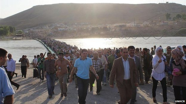 Syrians stream across the new pontoon bridge over the Tigris on 15 August 2013