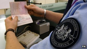 United Kingdom Immigration officer checking a passport at Heathrow Airport