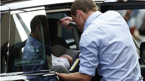 Prince William places his newborn son and his car seat into the car before leaving hospital on 23 July 2013
