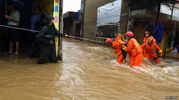 Rescuers carry a woman across a flooded street after Typhoon Utor hit Jiangyong county, Hunan province (17 August 2013)