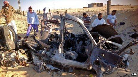 Egyptians gather near a wreckage of a car in El-Arish. Photo: July 2013