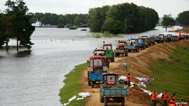 Soldiers and local residents reinforce an embankment to prevent flood from an overflowing river in Heihe, Heilongjiang province (17 August 2013)