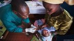 A nurse injects Chimene Kpakanale with her new baby at a Merlin-supported hospital in Obo, Central African Republic