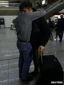 Glenn Greenwald and David Miranda embrace inside an airport