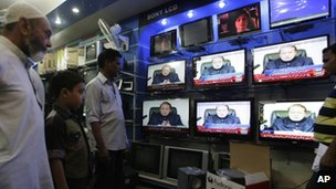 People in a Karachi shop watch Nawaz Sharif addressing the nation