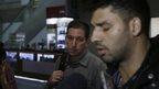 David Miranda being interviewed at an airport as Glenn Greenwald looks on