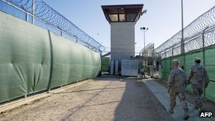 """file photo reviewed by the US military, show two members of the military walking out of the """"Camp Six"""" detention facility of the Joint Detention Group at the US Naval Station in Guantanamo Bay, Cuba 12 January 2012"""