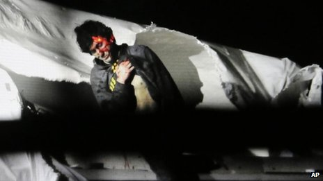 Massachusetts State Police photo, Dzhokhar Tsarnaev, bloody and dishevelled with the red dot of a sniper's rifle laser sight on his head, emerges from a boat at the time of his capture by law enforcement authorities in Watertown, Massachusetts 19 April 2013