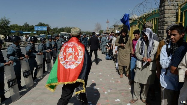 An Afghan football fan walks past fellow supporters queuing to watch their team play against Pakistan